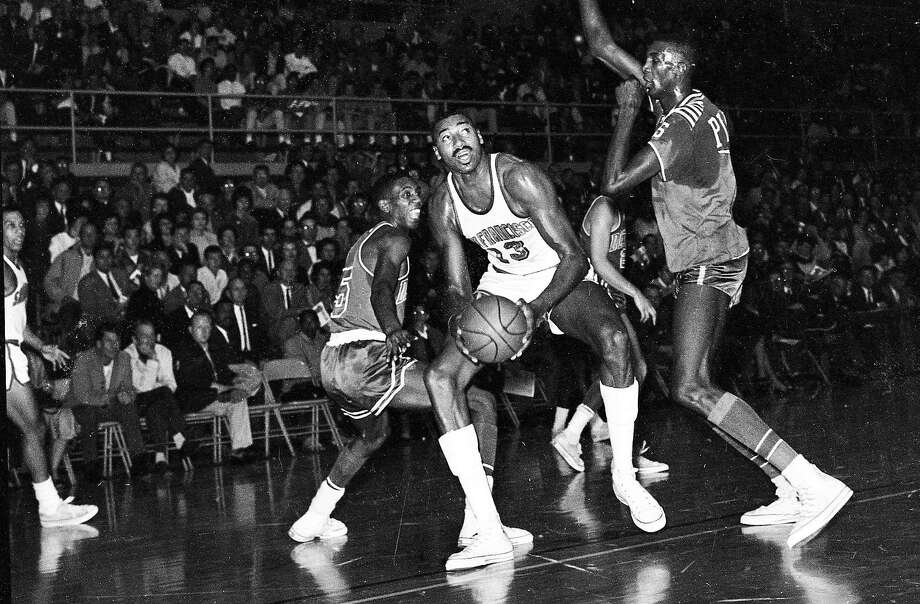 Wilt Chamberlain of the San Francisco Warriors is surrounded by Detroit Pistons during the Warriors' first game in S.F. at USF's Memorial Gym in 1962. Chamberlain had 50 points and the Warriors won in overtime. Photo: Joe Rosenthal, The Chronicle