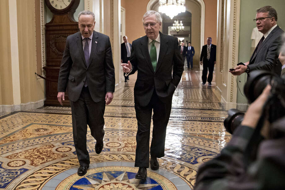 Senate Majority Leader Mitch McConnell, R-Ky. (right) talks to Senate Minority Leader Chuck Schumer, D-N.Y., while walking towards the Senate Chamber at the U.S. Capitol in Washington on Feb. 7, 2018. Photo: Bloomberg Photo By Andrew Harrer. / © 2018 Bloomberg Finance LP