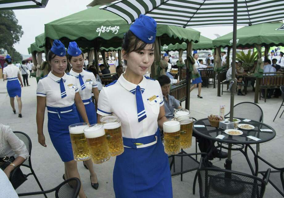 This photo taken on Aug. 12, 2016 shows a waitress carrying jugs of beer to guests before the opening of the first Pyongyang Taedonggang Beer Festival on the banks of the Taedong river in Pyongyang. The most recent festival to debut North Korea's new wheat beer was abruptly cancelled. Photo: Kim Won-Jin /AFP / Getty Images / This content is subject to copyright.