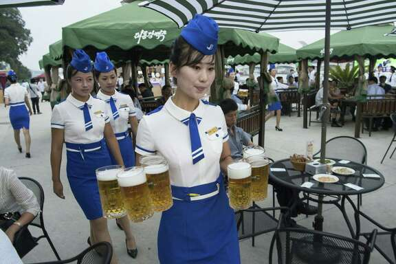 This photo taken on Aug. 12, 2016 shows a waitress carrying jugs of beer to guests before the opening of the first Pyongyang Taedonggang Beer Festival on the banks of the Taedong river in Pyongyang. The most recent festival to debut North Korea's new wheat beer was abruptly cancelled.