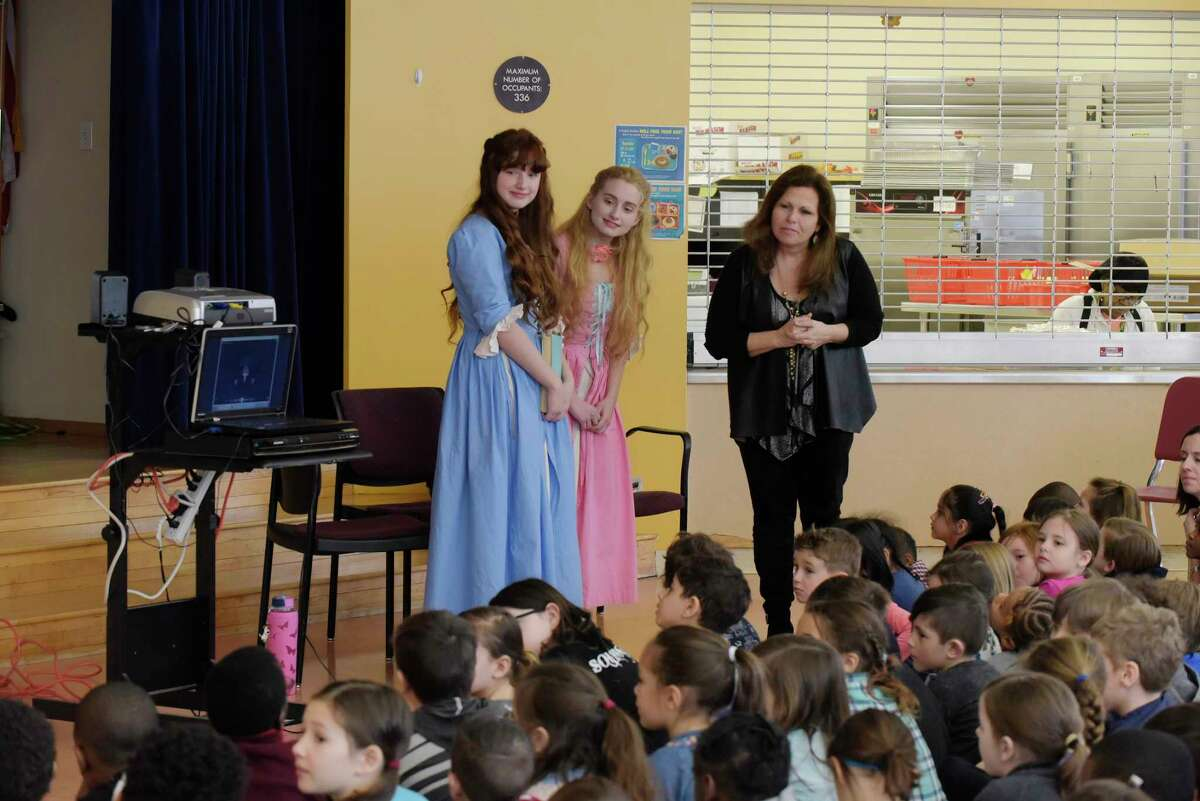 Sisters, Demetra, left, 15, and Callista, center, 17, Zorbas from Colonie, dressed as their characters from the television show, The Adventures of Snow White and Rose Red, and Ann Marie Lizzi, one of the producers, directors and editor of the series, talk with students at the Montessori Magnet School on Thursday, Feb. 8, 2018, in Albany, N.Y. Lizzi, has two children at the school and held an event to show the children how a television show is created. The show used all local actors and was filmed this past summer in and around the Saratoga Springs area. The series will be distributed through Amazon Prime sometime in the spring or early summer. A trailer for the show can be viewed on Prime. This Saturday there will be a screening of selected episodes from 10:00am to 4:00pm at the National Museum of Dance. Tickets for the screening can be purchased through www.eventbrite.com (Paul Buckowski/Times Union)