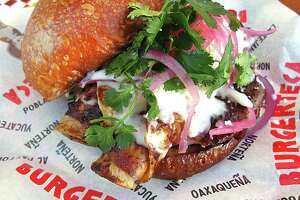 An enchilada burger with a beef patty, chile ancho, corn tortillas, queso fresco, crema, pickled red onions and cilantro from Burgerteca.