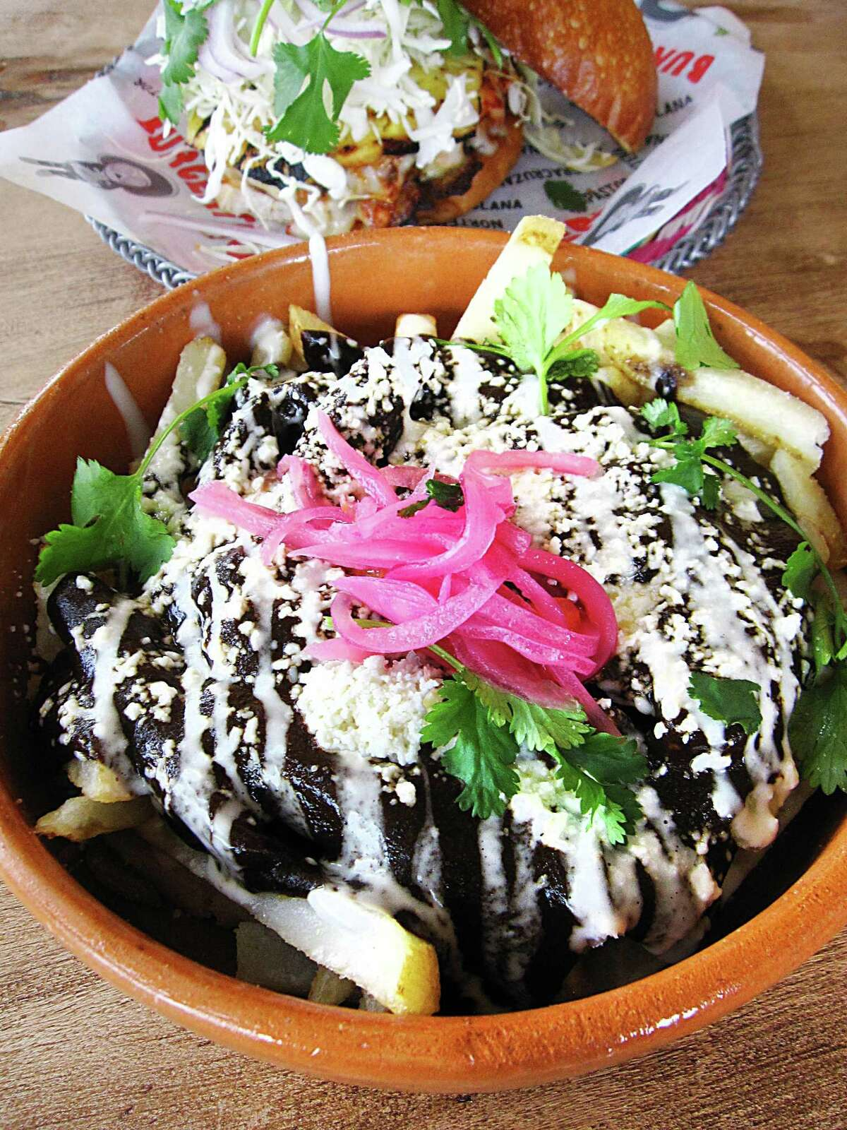 Mole fries with queso fresco and pickled onions and an al pastor burger from Burgerteca.