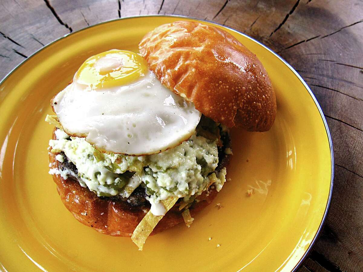 A chilaquiles burger with tortilla chip strips, salsa verde, crema, queso fresco, black beans and a fried egg from Burgerteca.
