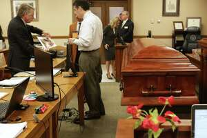 "Robert ""Dick"" Tips and his wife Kristin Tips stand at the courtroom door in the 131st Civil District Courtroom, as lawyers prepare for the trial, next to a coffin they had brought in for Tip's trial on Thursday, Feb. 8, 2018."