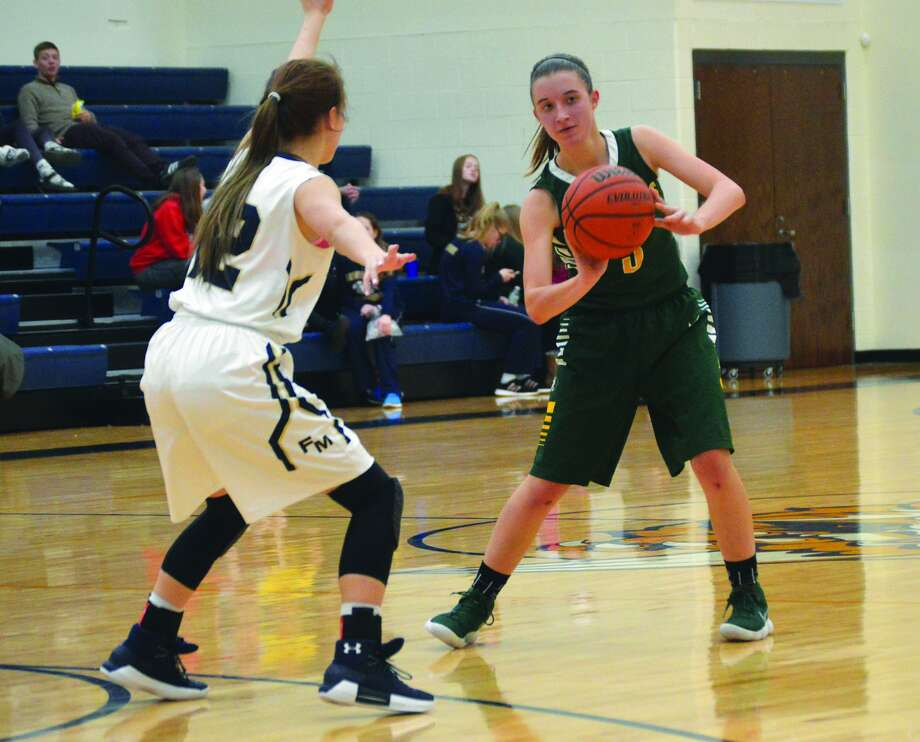 MELHS junior guard Sami Kasting, right, delivers a pass during a regular season game against Father McGivney.