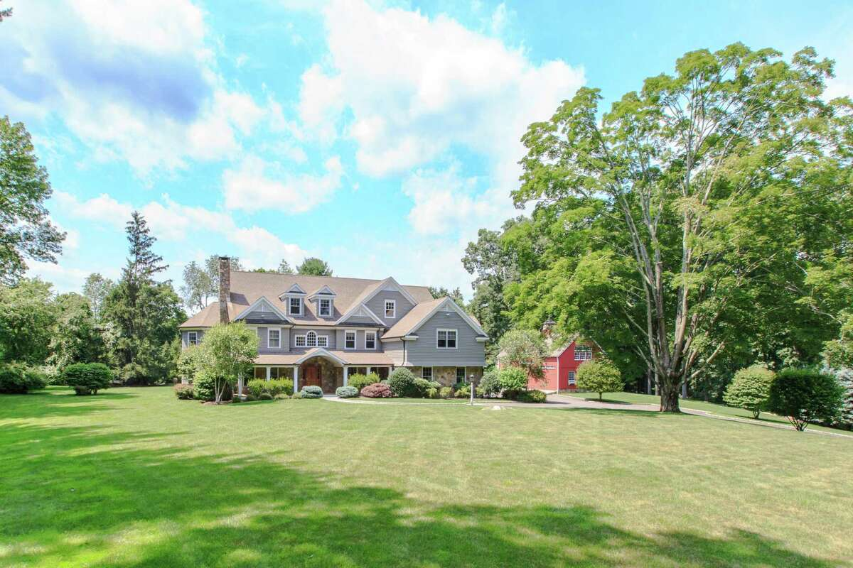 The gray shingle and stone colonial house with white trim and its red barn sit well back from the road on a level property of just over two acres.