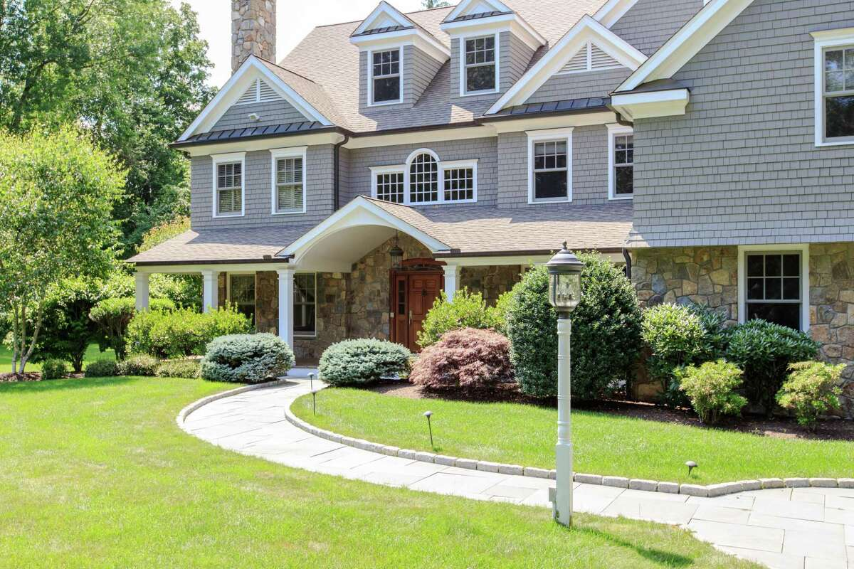 A bluestone path lined in Belgium block leads to the covered front entrance and covered front porch with columns.