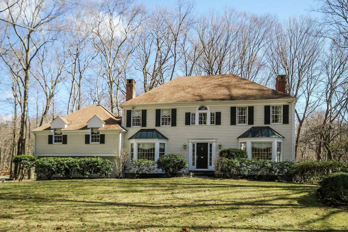 The cream-colored clapboard colonial house at 39 Black Alder Lane in Wilton's Cannondale neighborhood sits on a 1.14-acre level and gently sloping woodland property at the far end of a long cul-de-sac.