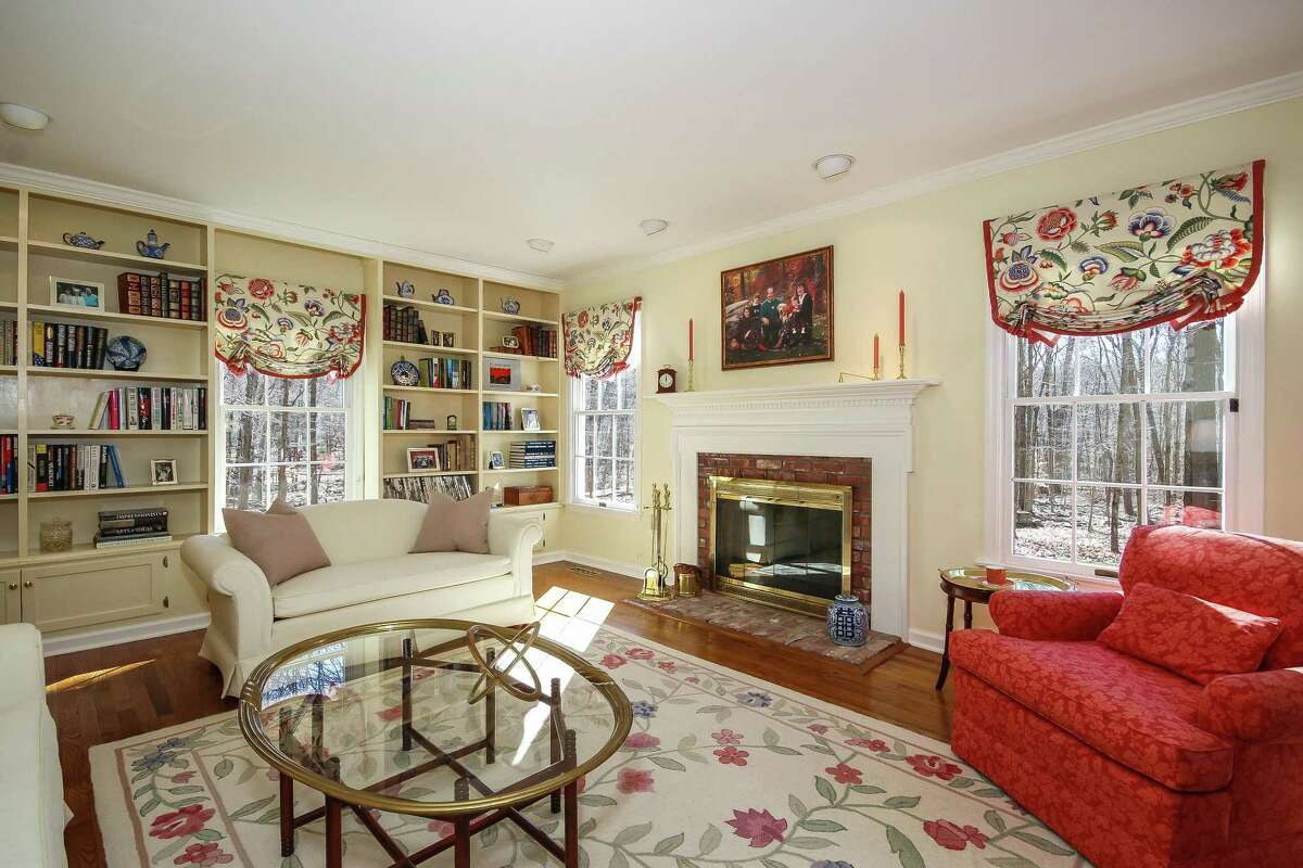 The formal living room has a red brick fireplace with a white wood mantel and a wall of built-on bookshelves with lower level cabinetry.
