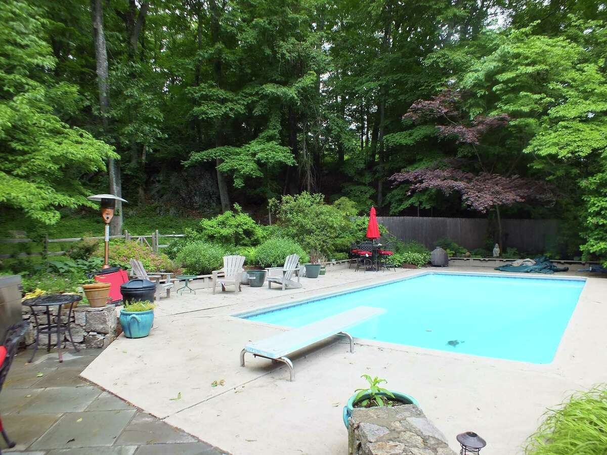 A second patio accessed from the upper level family room has an in-ground swimming pool with natural privacy screening provided by the many trees on the property.