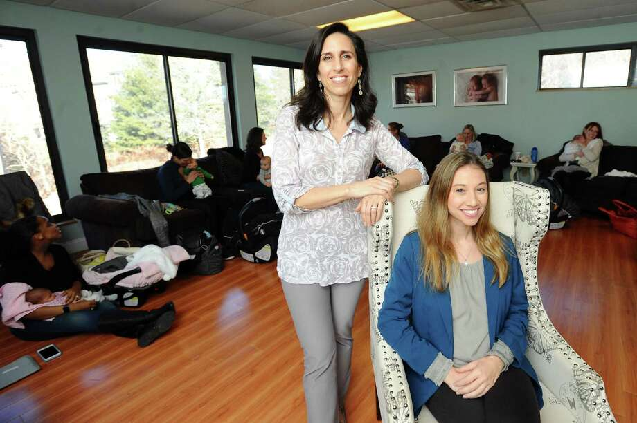 Stamford resident Natalie Telyatnikov, seated, and Cynthia Overgard pose for a photo following a postpartum support support group in Westport on Monday. Telyatnikov co-founded the group, which meet inside Overgard's HypnoBirthing space. Photo: Michael Cummo / Hearst Connecticut Media / Stamford Advocate
