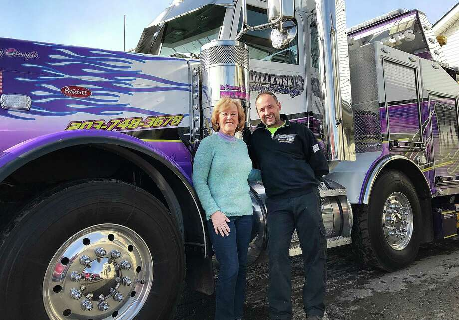 Karin and James Modzelewski, wife and son of the late Mark Modzelewski, stand in front of one of the business's tow trucks at their Danbury, Conn., location on Thursday, Feb. 8, 2018. Photo: Chris Bosak / Hearst Connecticut Media / The News-Times