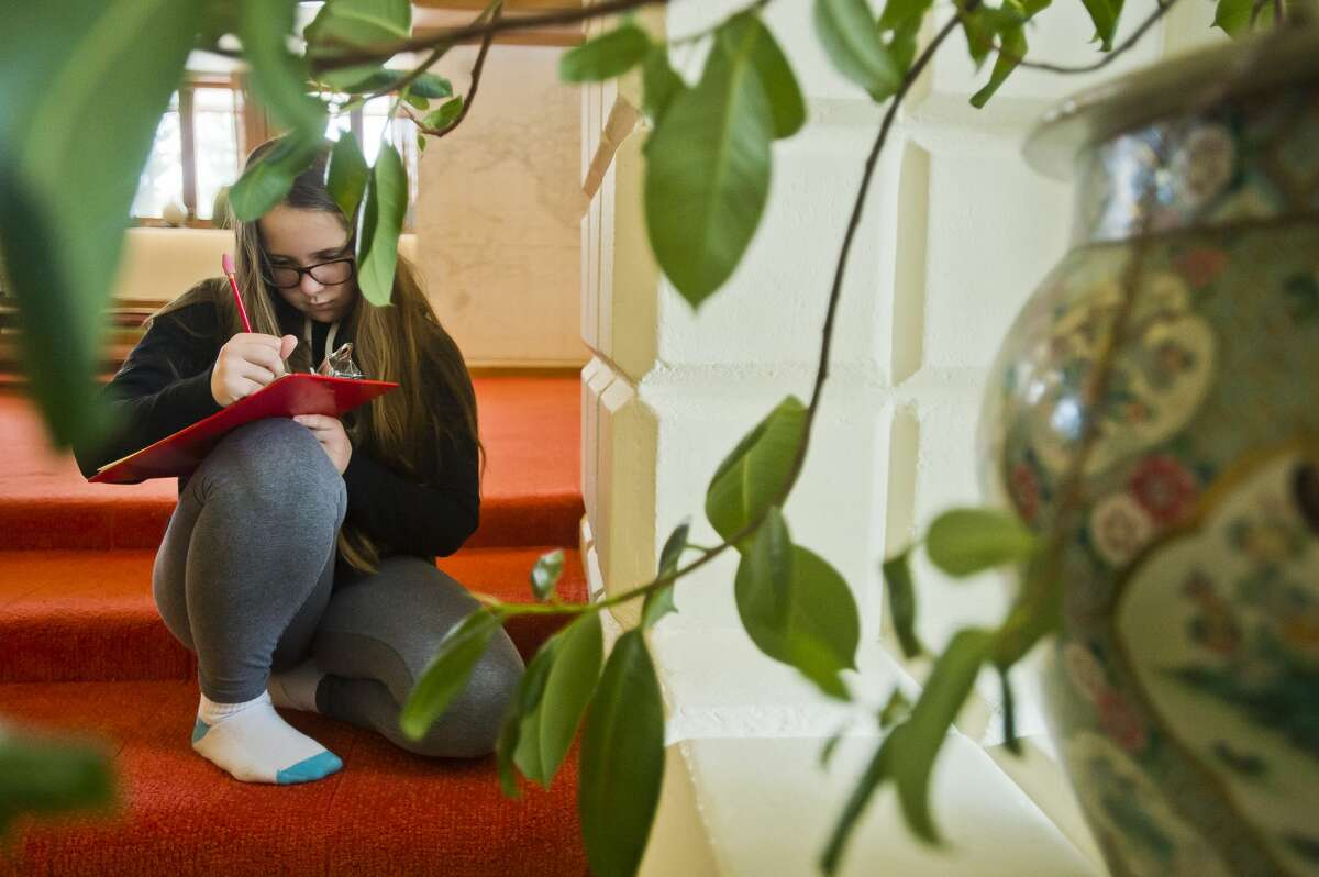 Paige Barnard, 12, observes a space inside the Alden B. Dow Home and Studio as she participates in a writing exercise on Thursday, Feb. 8, 2018. Spaces inside the home were arranged as if the home is being lived in, and the students used those details to produce fictional stories. (Katy Kildee/kkildee@mdn.net)