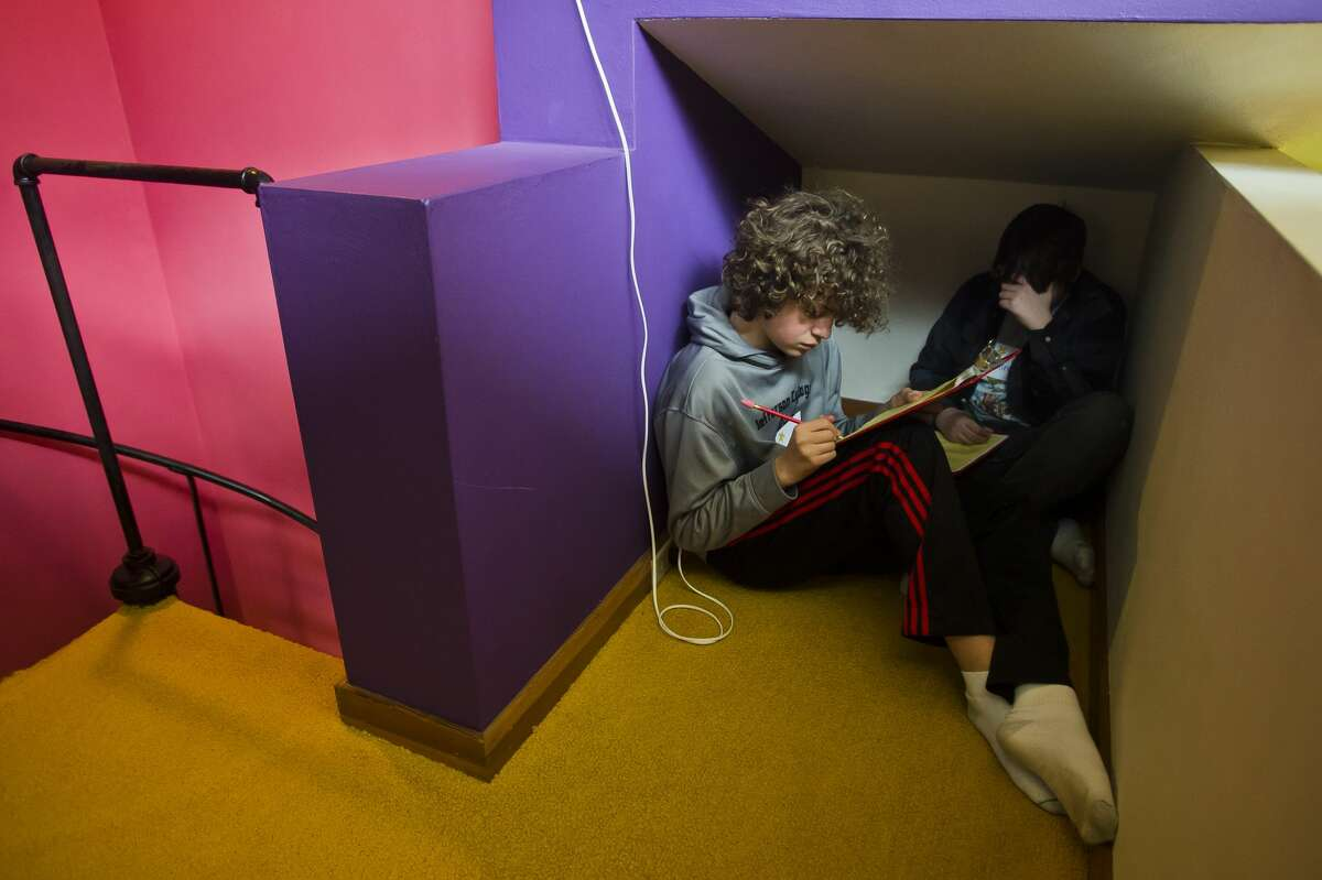 David Seidel, 12, left, and Alex Gregory, 13, right, participate in a writing exercise at the Alden B. Dow Home and Studio on Thursday, Feb. 8, 2018. Spaces inside the home were arranged as if the home is being lived in, and the students used those details to produce fictional stories. (Katy Kildee/kkildee@mdn.net)