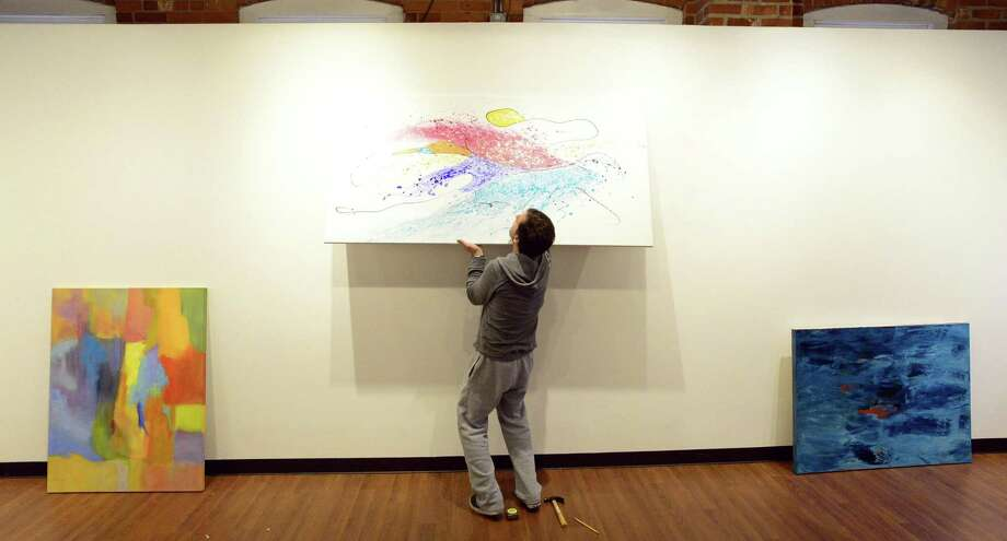 Mark Macrides of the Loft Artists Association installs a piece by Lisa Cuscuna, one of several artist that are part of a gallery of paintings for the upcoming Colorfields Exhibit on Wednesday, Feb. 7, 2018 in Stamford, Connecticut. The exhibit is part of a collaboration with the Stamford Museum and Nature Center and will open on Friday. Photo: Matthew Brown / Hearst Connecticut Media / Stamford Advocate