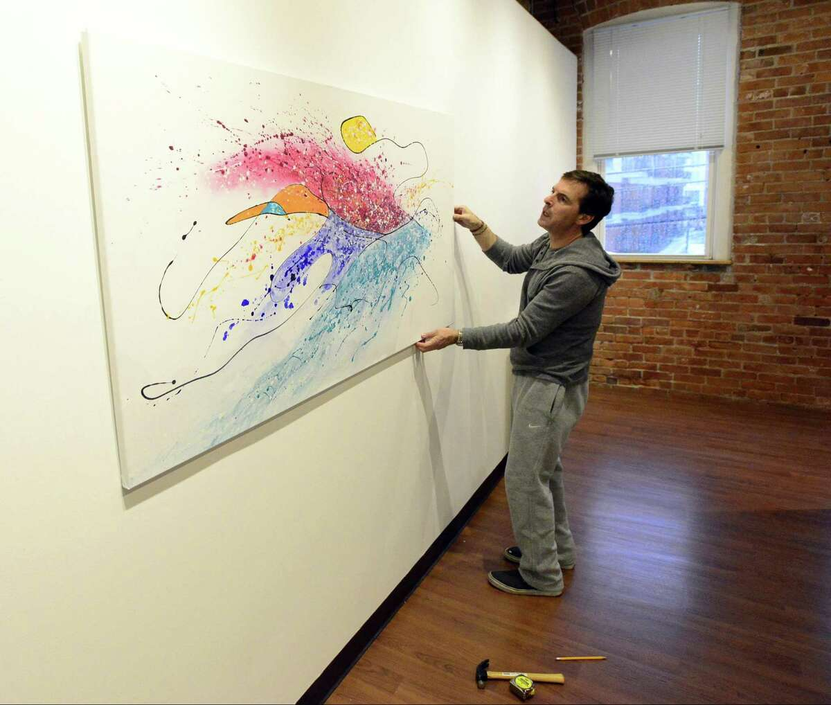 Mark Macrides of the Loft Artists Association installs a piece by Lisa Cuscuna, one of several artist that are part of a gallery of paintings for the upcoming Colorfields Exhibit on Wednesday, Feb. 7, 2018 in Stamford, Connecticut. The exhibit is part of a collaboration with the Stamford Museum and Nature Center and will open on Friday.