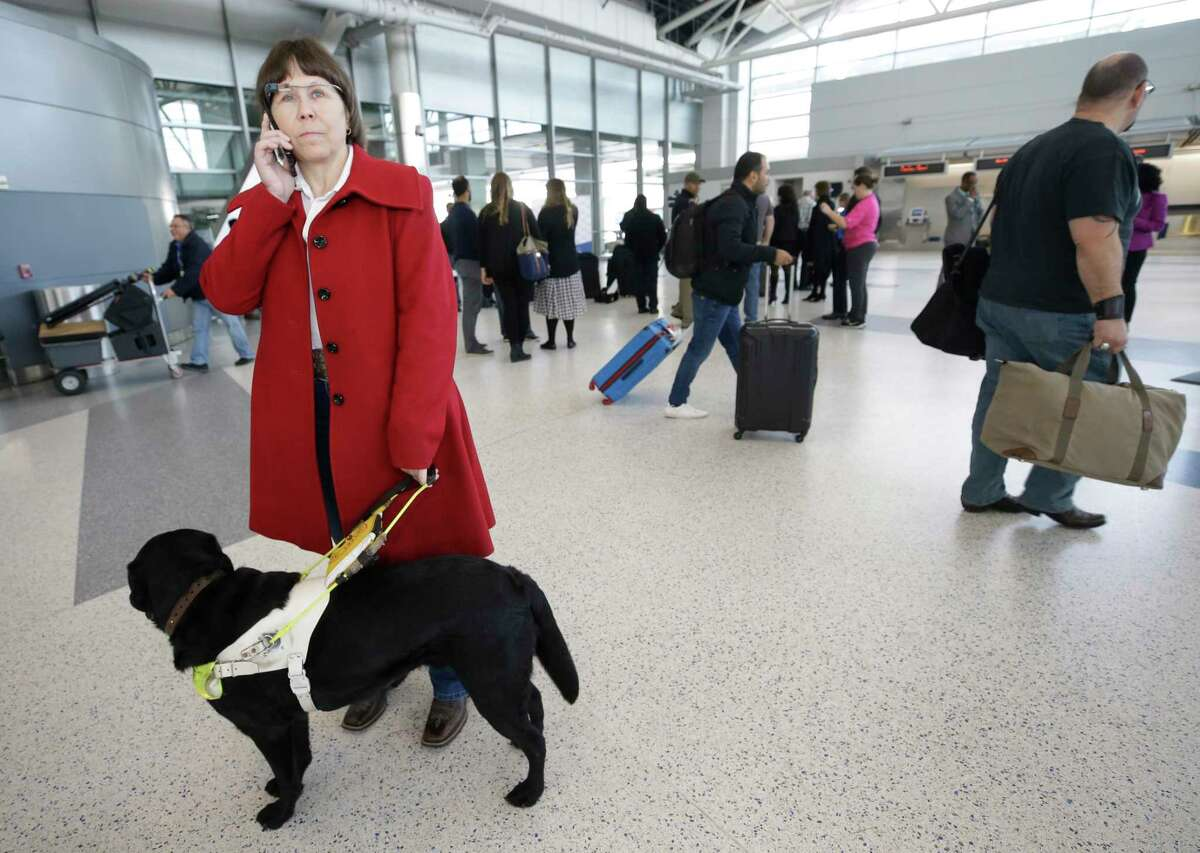 Donna Grahmann of Magnolia with her guide dog, Cruiser, talks to an Aira agent on the phone as she wears smart glasses during a demonstrates the Aira app in Terminal E at Bush Intercontinental Thursday, Feb. 8, 2018, in Houston. Blind and low vision people are connected to agents who assist them using the real-time livestream from the camera on the glasses. Houston Airport System has agreed to cover the costs of minutes used by Aira subscribers within the both airport terminals through the end of the year.