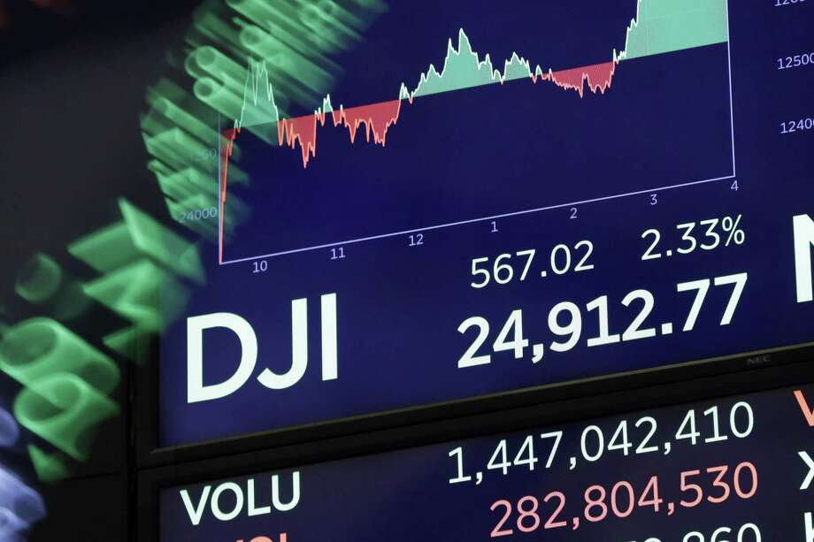 A board above on the trading floor of the New York Stock Exchange shows the closing number for the Dow Jones industrial average, Tuesday. The DJIA gained 567 points, or 2.3 percent, recouping nearly half of the 1,175-point plunge it took the day before. Photo: Richard Drew /Associated Press / AP
