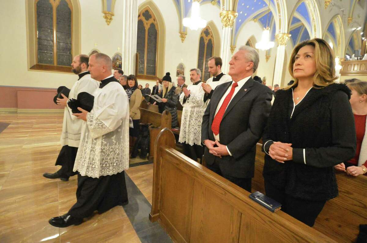 The processional into St. Mary's Roman Catholic Church passes Norwalk Mayor Harry Rilling and wife Lucia for a special mass to dedicate the new shrine and Our Lady of Norwalk statue, on Wednesday. The right panel has a painting of St. Mary's Church and the left panel shows an oyster fisherman in full gear, with the Norwalk islands in the background. The central panel depicts Mary's throne with saints surrounding.