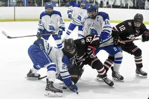 Darien Bennett McDermott (22) and New Canaan Sam Augustine (27) face off during a FCIAC boys ice hockey game at the Darien Ice Rink in Darein, Conn. on Saturday, Dec. 23, 2017. Darien defeated New Canaan 8-1.