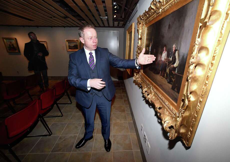 Ciaran Cannon, Irish Minister of State at the Department of Foreign Affairs and Trade, views the oil painting, Mending the Nets, from 1886 by Howard Helmick during a visit to Quinnipiac University's Great Hunger Museum in Hamden on February 8, 2018. Photo: Arnold Gold / Hearst Connecticut Media / New Haven Register