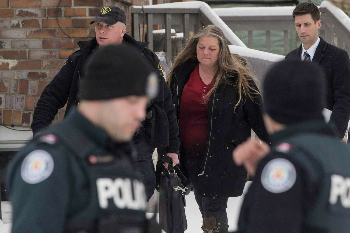 Forensic anthropologist professor Kathy Gruspier, center, walks with police officers at a property where alleged serial killer Bruce McArthur worked, Thursday, Feb. 8, 2018 in Toronto.
