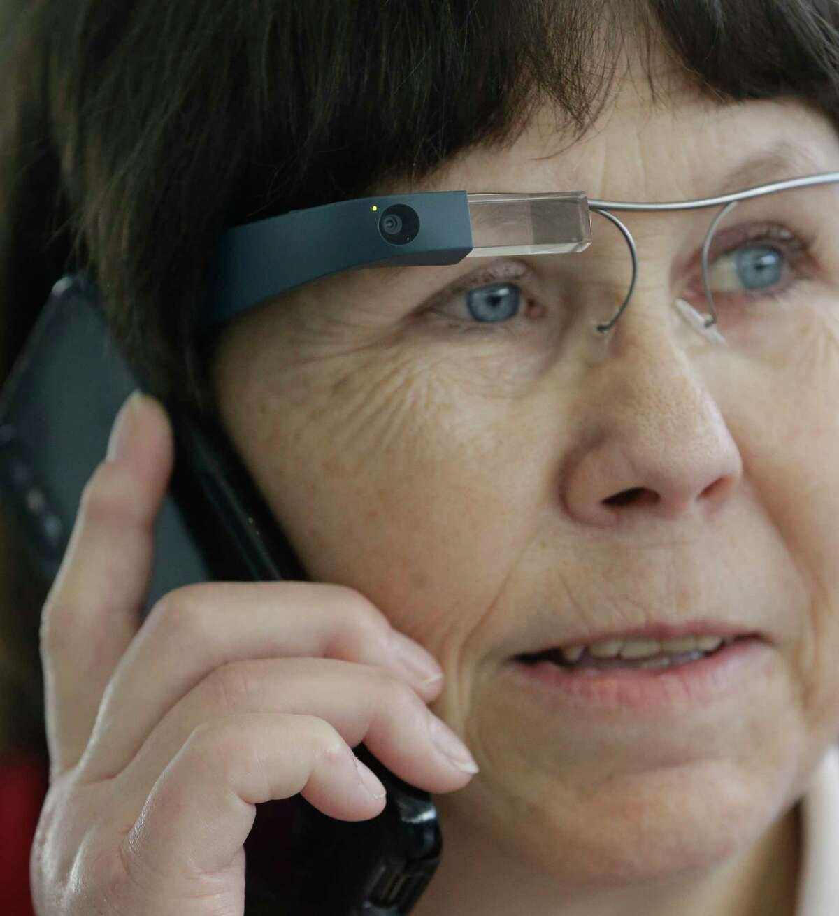 Donna Grahmann of Magnolia with her guide dog, Cruiser, talks to an Aira agent on the phone as she wears smart glasses during a demonstrates the Aira app in Terminal E at Bush Intercontinental Thursday, Feb. 8, 2018, in Houston. ( Melissa Phillip / Houston Chronicle )