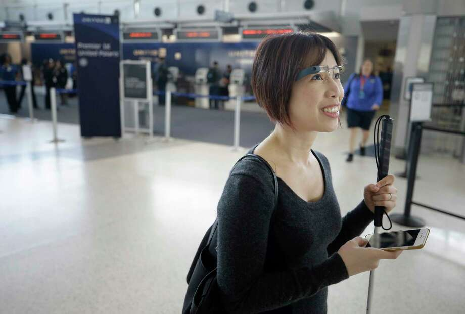 Christine Ha, of Houston wears smart glasses as she demonstrates the Aira app in Terminal E at Bush Intercontinental Thursday, Feb. 8, 2018, in Houston. ( Melissa Phillip / Houston Chronicle ) Photo: Melissa Phillip, Houston Chronicle / © 2018 Houston Chronicle