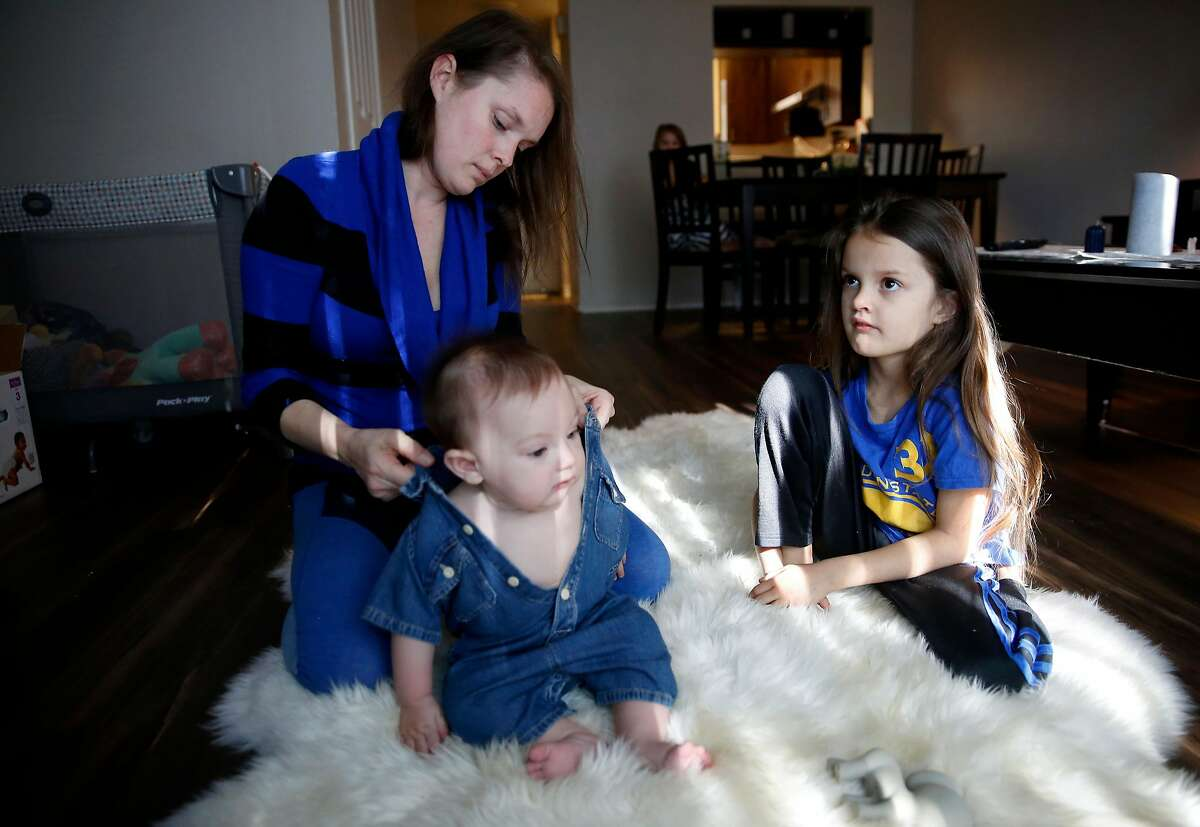 Angel Edwards, left, dresses her son Jakaiyah, 7 months, as her daughter Arilyn, 6, watches t.v. in their new residence, a Petaluma townhouse, on Sunday, February 4, 2018. The Edwards family lost nearly everything as the Tubbs Fire destroyed their Santa Rosa home last October.