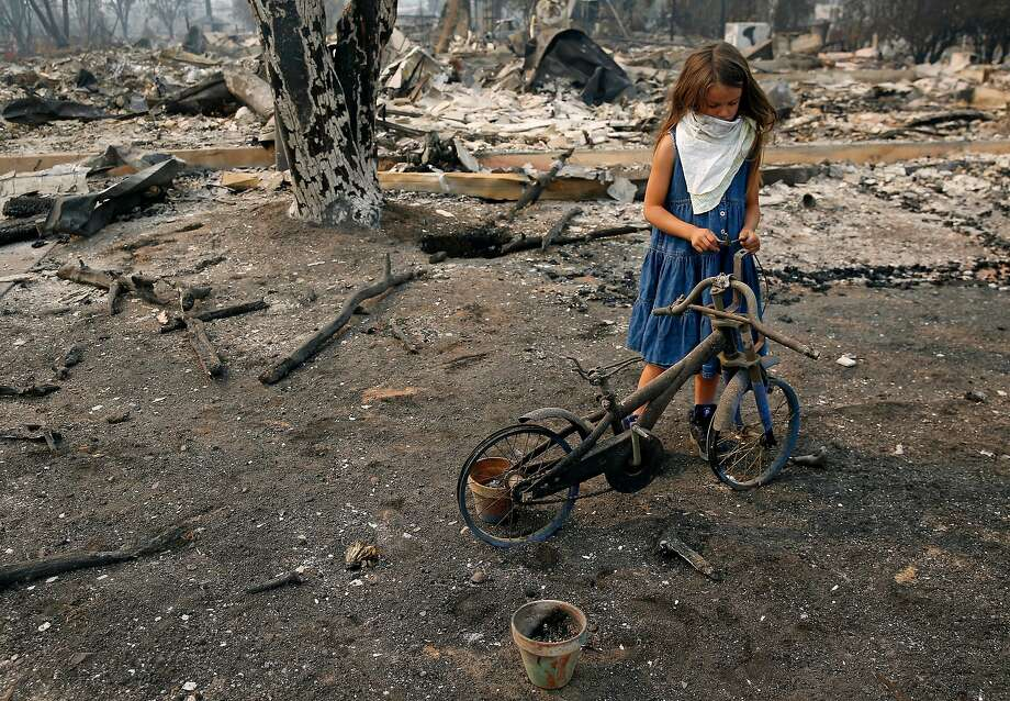 Arilyn Edwards, 6, stands beside her bike in front of the rubble of her Santa Rosa home on Oct. 10. The bike, which was a gift for her 6th birthday on Oct. 6, was destroyed as fire ripped through her neighborhood. Photo: Guy Wathen, The Chronicle