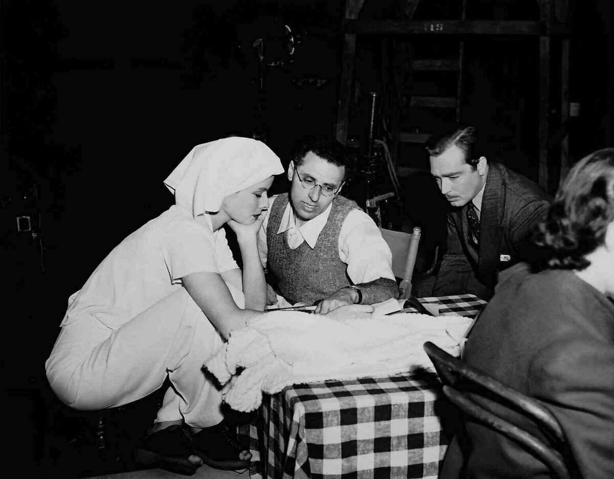 Katharine Hepburn (left) works with director George Cukor (center) and actor John Howard on