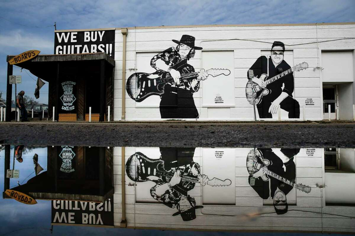 A mural of Stevie Ray Vaughan and Freddie King garnishes the side of Rockin' Robin Guitars, which owner Bart Wittrock is putting on the market after more than 45 years in business.