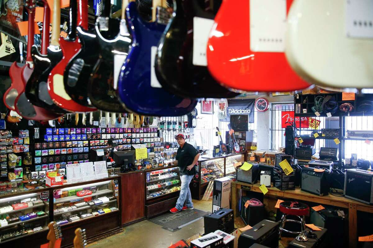 Customer Thomas Coffman surveys the Rockin' Robin Guitars store while checking out Thursday, Feb. 8, 2018 in Houston. After more than 45 years of being in business, owner Bart Wittrock is putting the store on the market in hopes of finding a new and energetic owner. (Michael Ciaglo / Houston Chronicle)