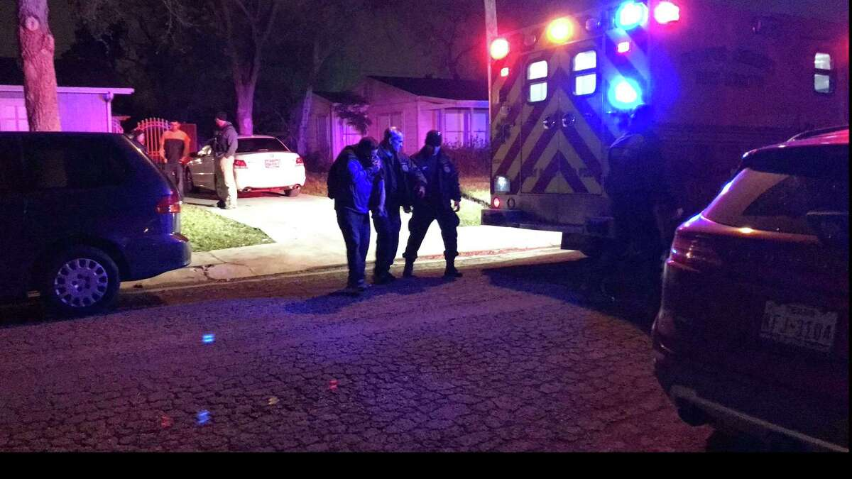Medics and officers escort a man as he walks to an ambulance in Corpus Christi, Texas. A man believed to be in his 30s is in police custody after four people were stabbed Wednesday, Feb. , 7, 2018