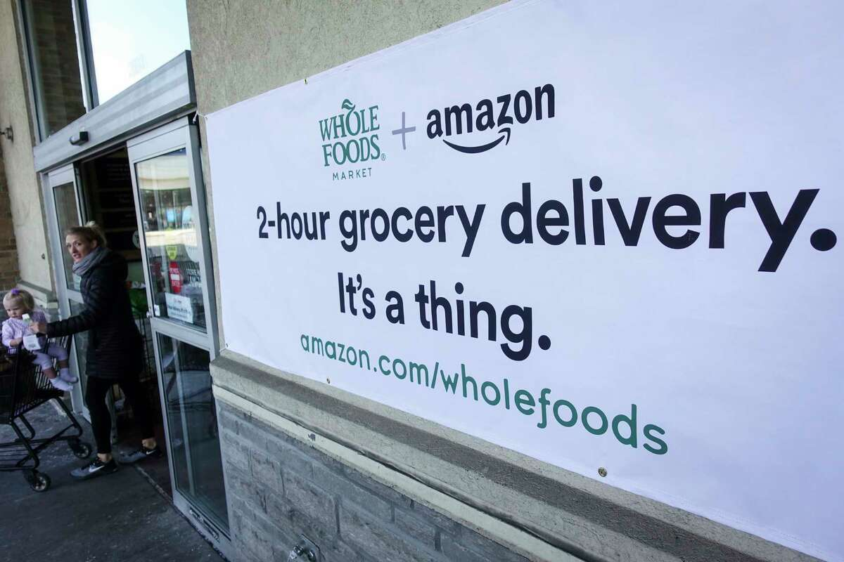 A sign promoting the Amazon Prime Now delivery service is displayed outside a Whole Foods store, Thursday, Feb. 8, 2018, in Cincinnati. Amazon, which owns Whole Foods, plans to roll out two-hour delivery at the organic grocer this year to those who pay for Amazon's $99-a-year Prime membership. Amazon.com Inc. said deliveries started Thursday in Austin, Texas; Cincinnati; Dallas; and Virginia Beach, Va. (AP Photo/John Minchillo)