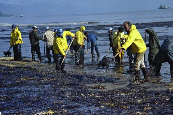 FILE - In this Feb. 6, 1969, file photo, state forestry conservation crews made up of prison convicts clean up oil-soaked straw after an oil spill on the beach in Santa Barbara, Calif. California commissions that oversee coastal lands and water pushed the Trump administration to leave the state out of plans to expand offshore drilling, warning the state would block the construction of pipelines to get oil back to land. (AP Photo/Wally Fong, file)