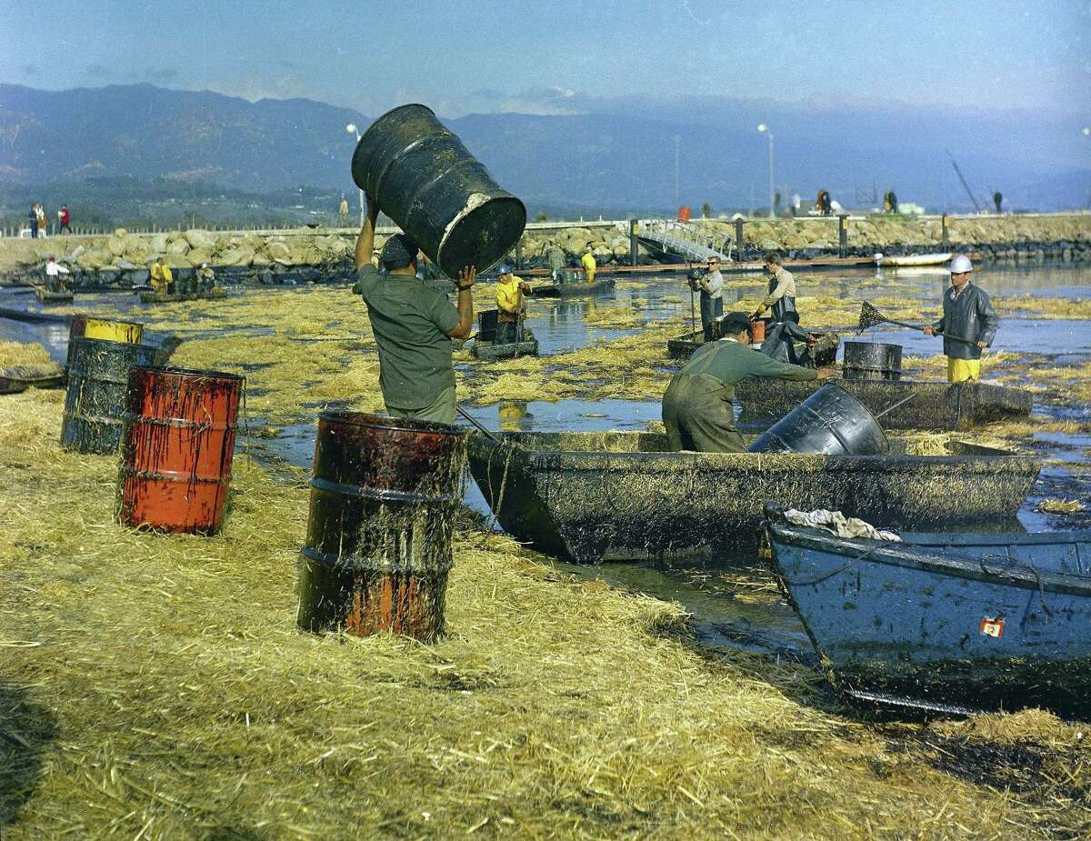 FILE - In this Feb. 7, 1969 file photo, workers collect oil-soaked straw from the beach at Santa Barbara Harbor, Calif., following a leak from an off-shore well that covered area beaches. California commissions that oversee coastal lands and water pushed the Trump administration to leave the state out of plans to expand offshore drilling, warning the state would block the construction of pipelines to get oil back to land. The agencies weighed in ahead of a public meeting Thursday, Feb. 8, 2018, in Sacramento. (AP Photo, FILE)