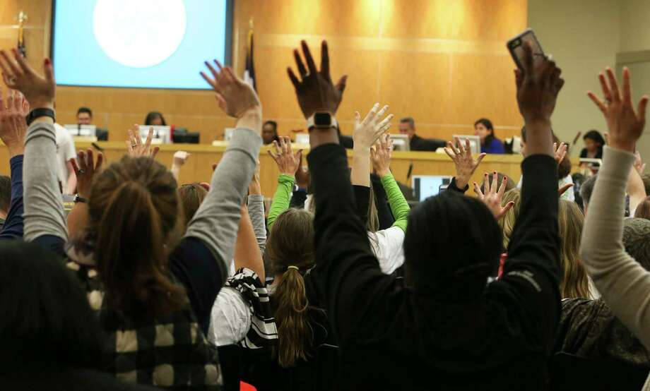 Participants stand up and raise their hands to agree with a speaker during a Houston ISD Board of Trustees public meeting at Hattie Mae White Educational Support Center on Thursday.  Photo: Yi-Chin Lee, Houston Chronicle / © 2018  Houston Chronicle