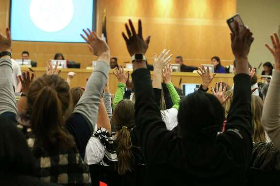 Participants stand up and raise their hands to agree with a speaker during a Houston ISD Board of Trustees public meeting at Hattie Mae White Educational Support Center on Thursday.