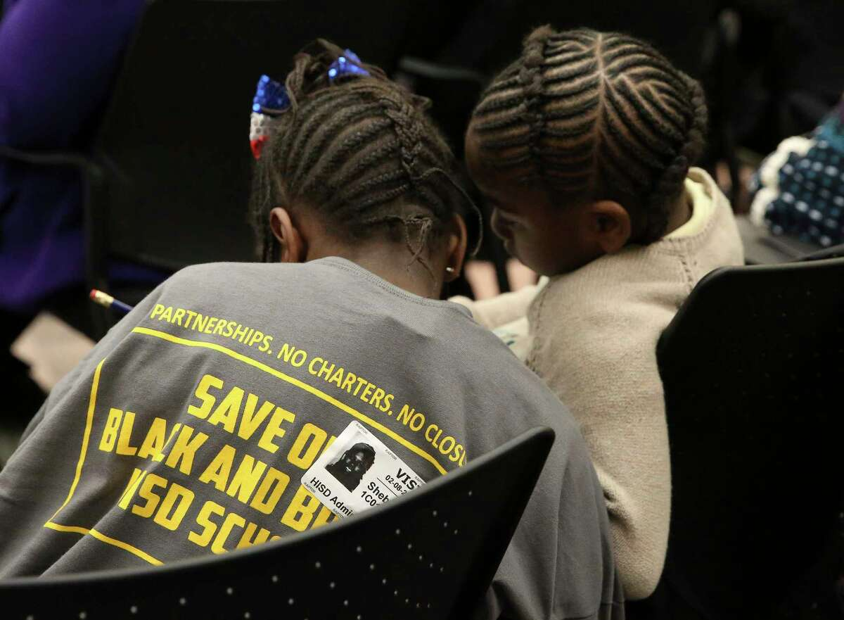 """Ashford Elementary students Imani Ibrahim, in a """"Save Our Black and Brown HISD Schools"""" t-shirt, and her cousin Harmony Green talk to each other while attending Houston ISD Board of Trustees public hearing at Hattie Mae White Educational Support Center on Thursday, Feb. 8, 2018, in Houston. It was the first hearing from the HISD community for the first time since plans were announced for major changes at 14 low-performing schools, and the hundreds came to the hearing. The cousins' school was not among the 14 schools but their family show up at the hearing to support the schools to remain open."""