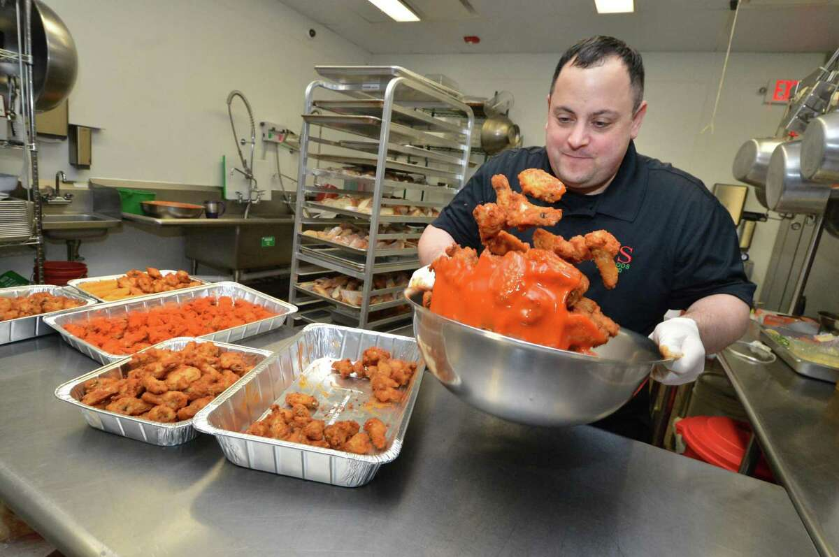 Albert Pizzirusso, Owner at A & S Fine Foods on Westport Ave. in Westport tosses some buffalo sauce on a batch of wings as he prepares nearly 200 pounds of wings for customers and clients on Super Bowl Sunday. Along with wings they made nearly 100 feet of subs in various sizes from regular to 5-foot Italian Combos on Sunday February 4, 2018 in Westport Conn