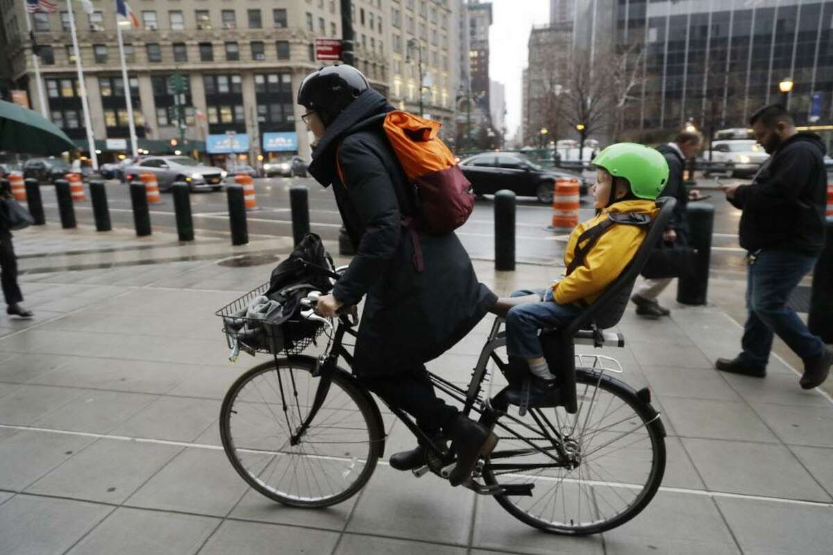 A woman commutes by bicycle with her son riding in back.