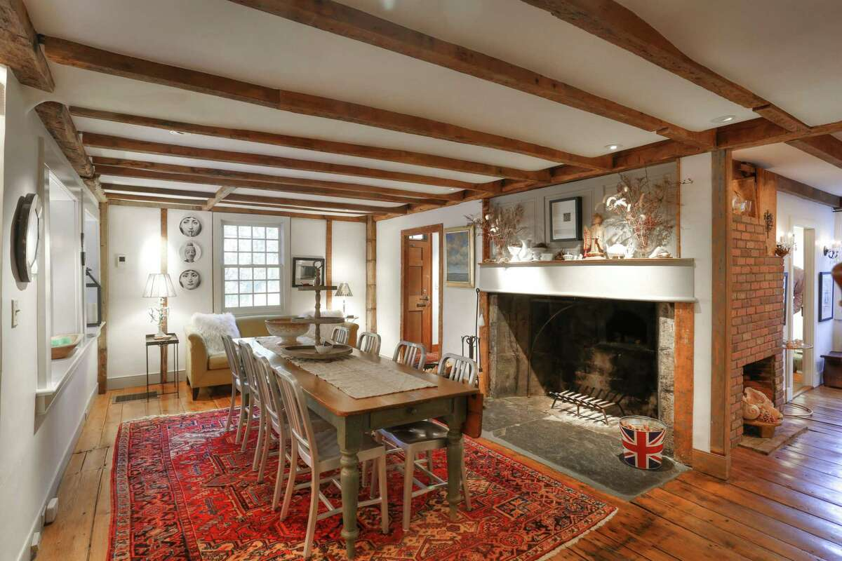 The formal dining room has the first of the home's four fireplaces, and exposed beams.