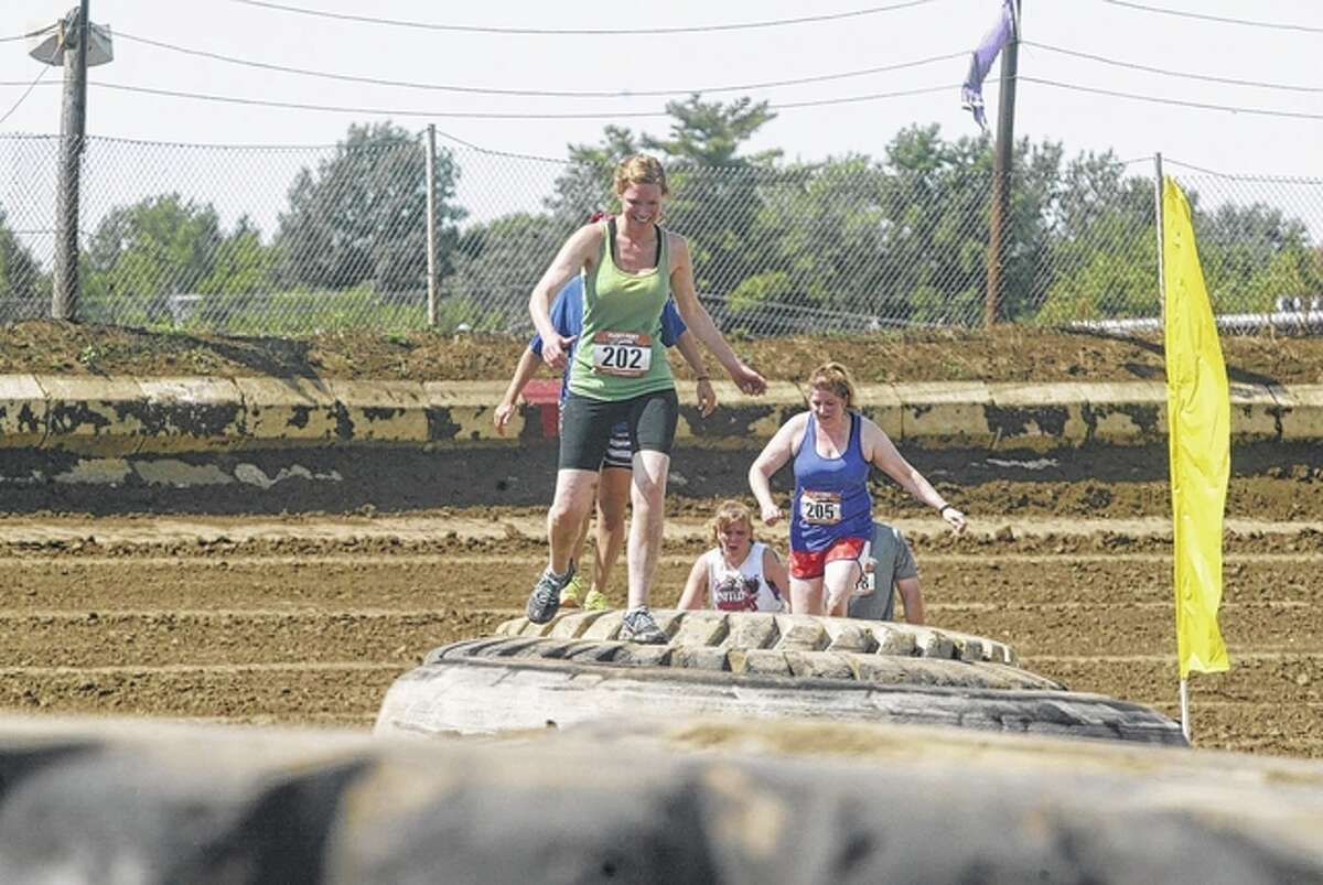 United Warriors Xtreme Race participants tackle the tire obstacle Saturday at the Morgan County Fairgrounds. Nearly 300 runners competed in the race, which raised money for 34 Prairieland United Way-supported agencies.