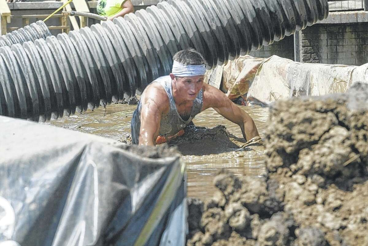 An unidentified runner crawls through the mud pit in front of the Morgan County Fairgrounds' grandstand Saturday during the United Warriors Xtreme Race.