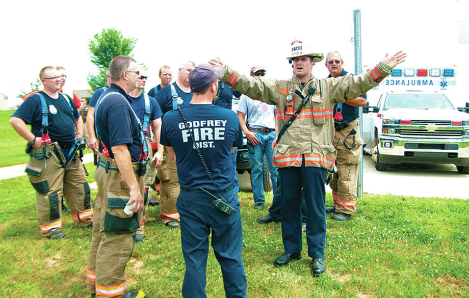 Godfrey Fire Chief Erik Kambarian gives out final instructions Saturday to his firefighters about going out around the perimeter of where the Chevrolet Tracker came to a rest after going airborne into the cornfield Friday night.