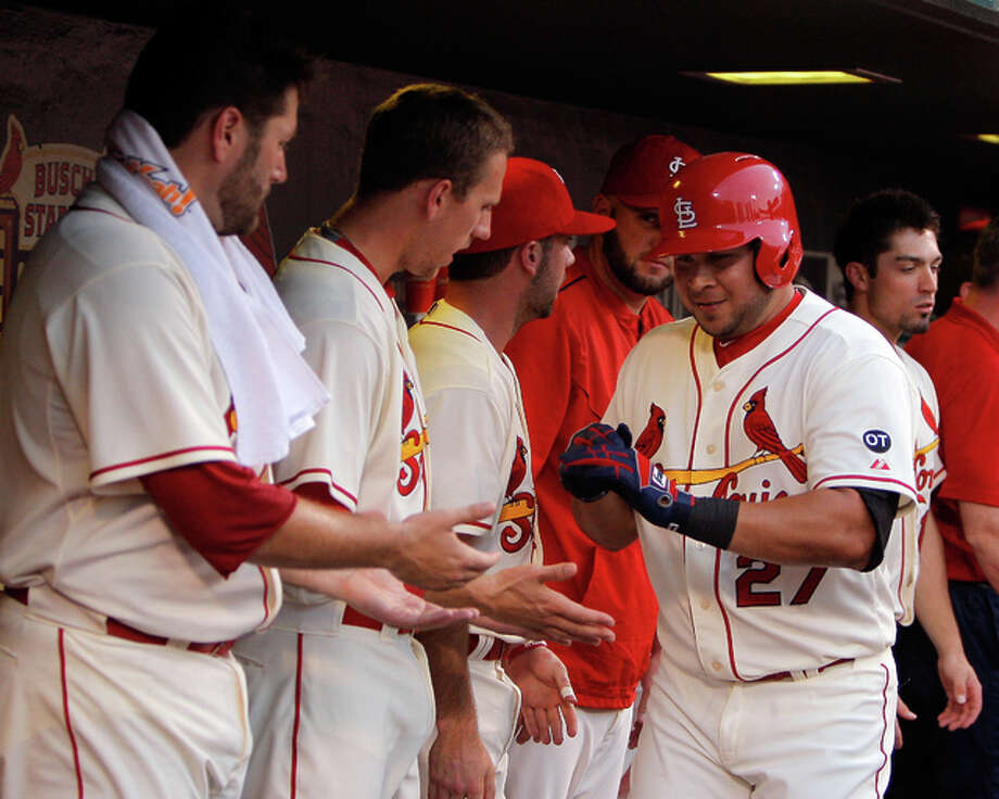 The Cardinals' Jhonny Peralta (right) is congratulated by teammates in the dugout after hitting a solo home run during the fourth inning against the Rockies on Saturday night at Busch Stadium.