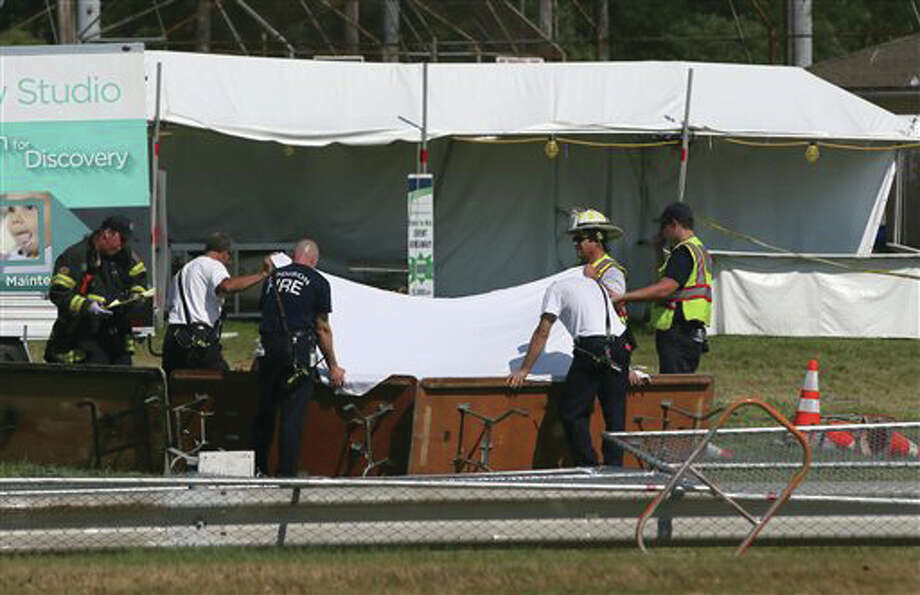Police and fire officials hold up a sheet over a body following a fatal tent collapse at the Prairie Fest in Wood Dale, Ill., Sunday. Several people were injured after the tent collapsed at the festival in suburban Chicago, according to the Chicago Tribune.