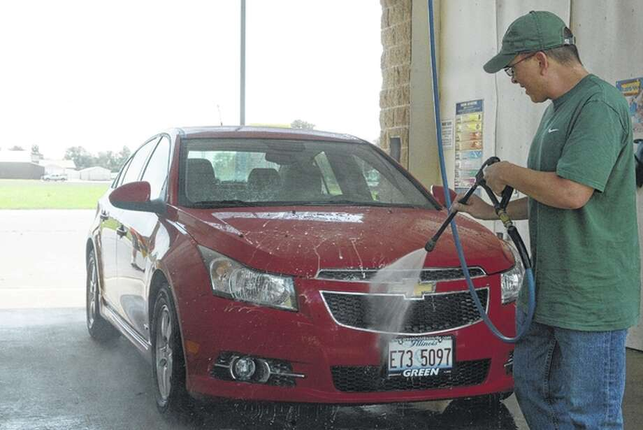 Cory West sprays his Chevy Cruze on a warm Monday afternoon at Quick Lane Car Wash in South Jacksonville.